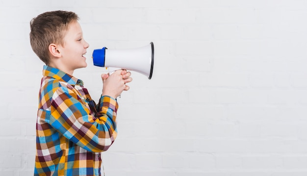 Primer plano de un niño gritando en voz alta en el megáfono contra el fondo blanco Foto gratis