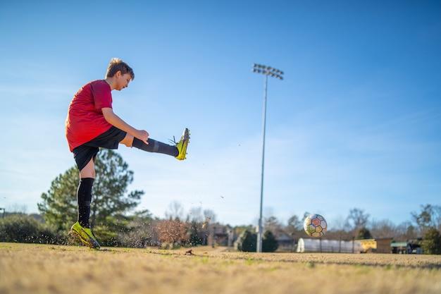 Primer plano de un niño jugando al fútbol en el campo con un uniforme rojo Foto gratis