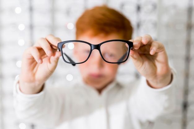 Primer plano del niño mostrando anteojos de montura negra en la tienda de óptica Foto gratis