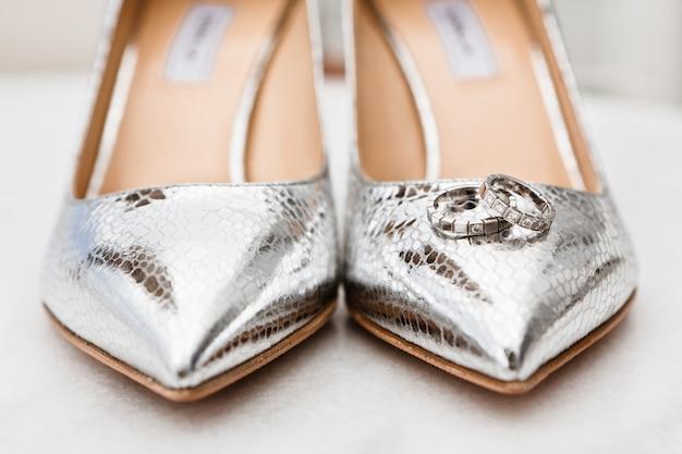 Primer plano de las novias zapatos plateados dedos de los pies y anillos de boda en el piso de mármol, enfoque selectivo Foto Premium