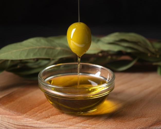 Primer plano de oliva y aceite ecológico Foto gratis