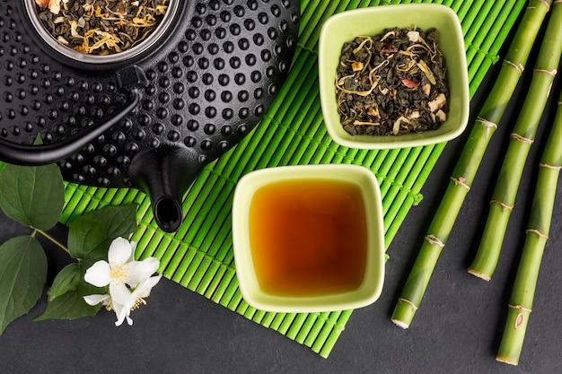 Primer plano de palo de bambú y té seco con ramita de flor de jazmín blanco Foto gratis