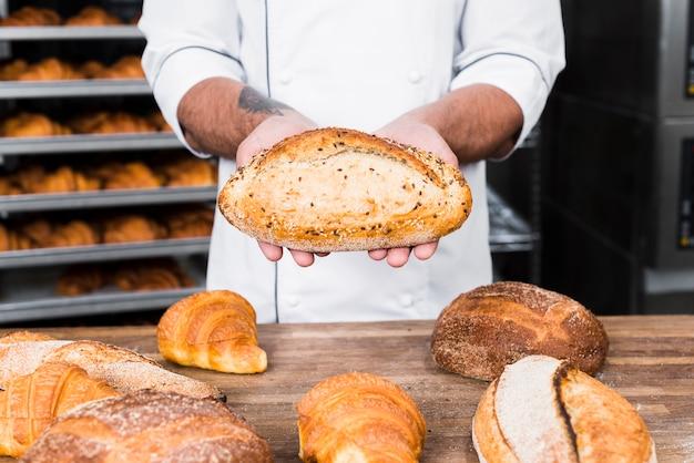 Primer plano de un panadero hombre sosteniendo pan recién horneado Foto gratis