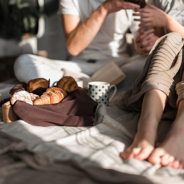 Primer plano de pareja con croissant y café en el desayuno Foto gratis