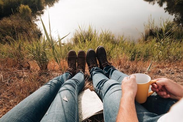 Primer plano de pareja sentada junto al lago Foto gratis