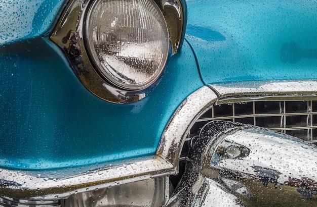 Primer plano de la parte delantera de un coche azul, incluidas las luces y el parachoques Foto gratis
