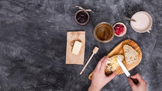 Primer plano de una persona agregando la mantequilla con un cuchillo; mermelada de frambuesa y miel sobre fondo negro con textura Foto gratis
