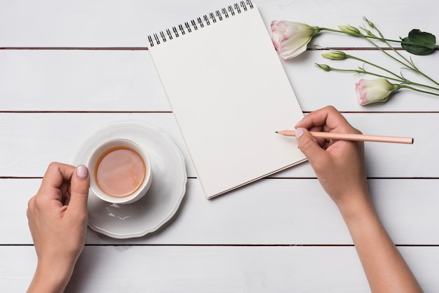 Primer plano de una persona escribiendo en el bloc de notas con una taza de teta sobre un escritorio de madera Foto gratis