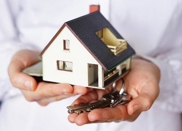 Primer plano de una persona pensando en comprar o vender una casa Foto gratis