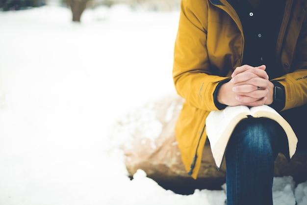 Primer plano de una persona sentada sobre una roca con la biblia en la rodilla y rezando Foto gratis