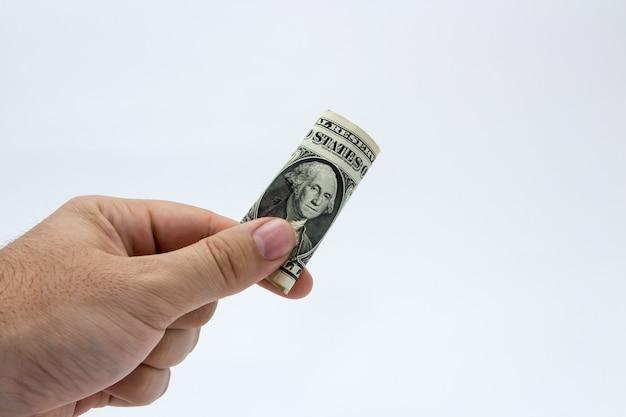 Primer plano de una persona sosteniendo un billete de un dólar sobre un fondo blanco. Foto gratis