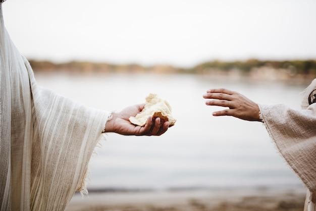 Primer plano de una persona vestida con un manto bíblico dando pan a otra persona Foto gratis