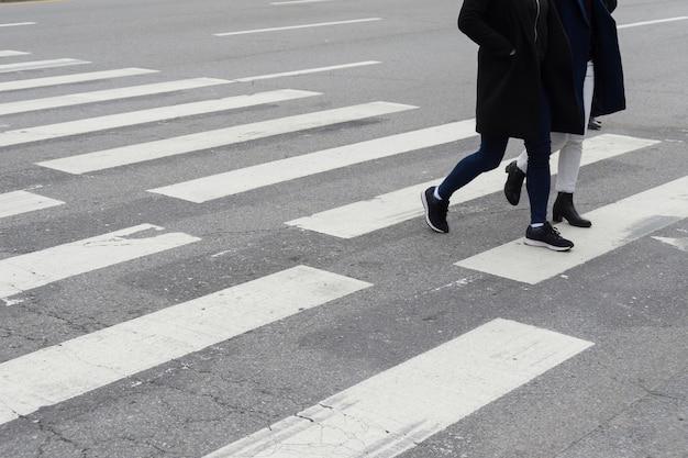 primer-plano-personas-no-identificadas-piernas-cruzando-calle_40555-7