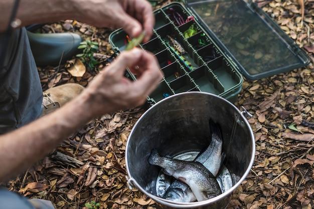 Primer plano de un pescador que pone en cebo Foto Premium