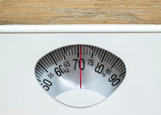 Primer plano de peso escalas sobrepeso y concepto de obesidad. Foto gratis