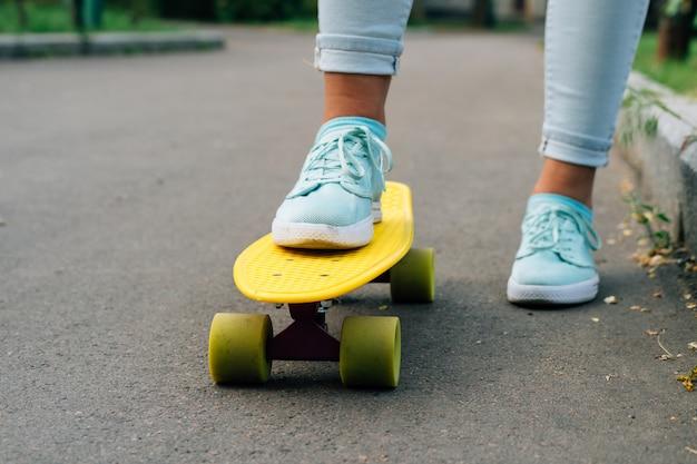 Primer plano de las piernas femeninas en blue jeans y zapatillas de deporte de pie en un monopatín amarillo Foto Premium