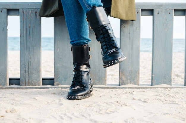 Primer plano de piernas femeninas en botas negras y jeans