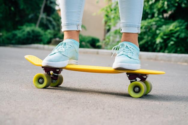 Primer plano de piernas femeninas en vaqueros y zapatillas de deporte de pie en un monopatín amarillo Foto Premium