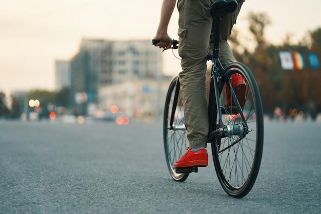 Primer plano de las piernas del hombre casual en bicicleta clásica en la carretera de la ciudad Foto gratis