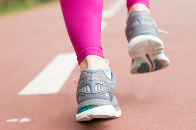 Primer plano de pies femeninos en calzado deportivo en el estadio Foto gratis