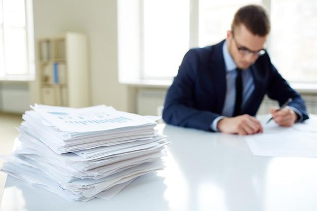 Primer plano de pila de documentos con ejecutivo de fondo Foto gratis
