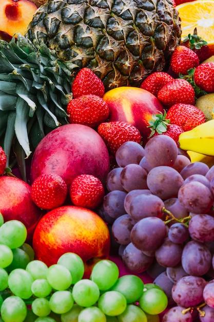 Primer plano de piña; fresa; uvas y manzana Foto gratis