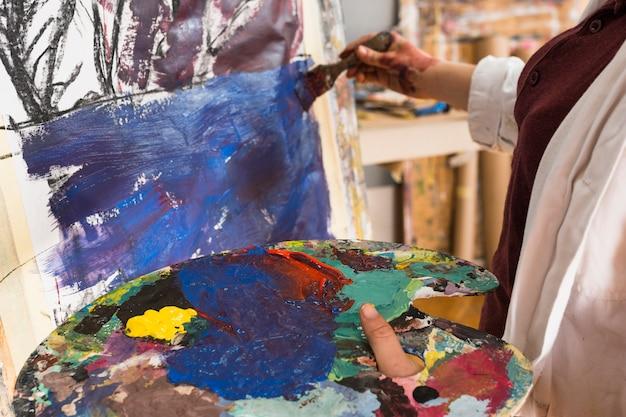 Primer plano de la pintura de la mano de la mujer sobre lienzo con la celebración de paleta desordenada Foto gratis