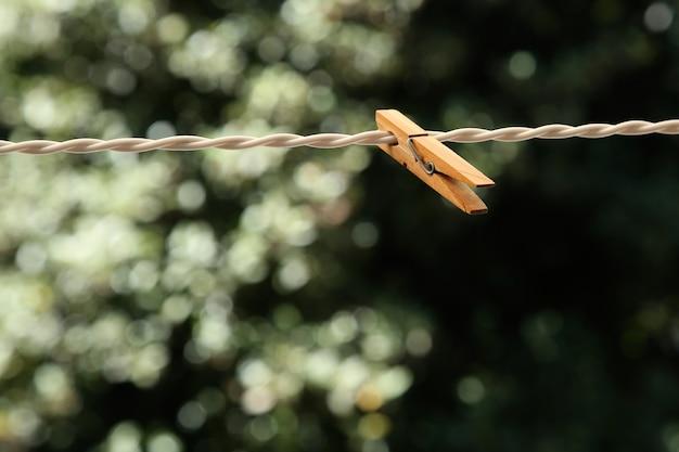 Un primer plano de una pinza de madera sobre un alambre con un fondo natural borroso Foto gratis