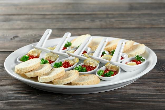 Primer plano de un plato grande, servido para un restaurante buffet con un sabroso aperitivo elaborado con caviar rojo, pan blanco, rodajas de limón y nata. se ve muy delicioso y bueno para banquetes y catering. Foto gratis