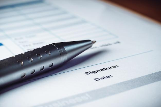 Primer plano de la pluma de plata están firmando los documentos del acuerdo de la política del contrato. firma de contrato legal. Foto Premium
