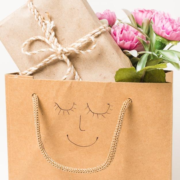 Primer plano de un ramo de flores y una caja de regalo envuelta en una bolsa de papel con cara dibujada a mano en ella Foto gratis