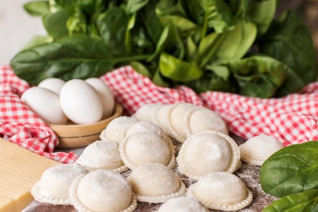 Primer plano de raviolis crudos circulares con espinacas y huevos Foto gratis