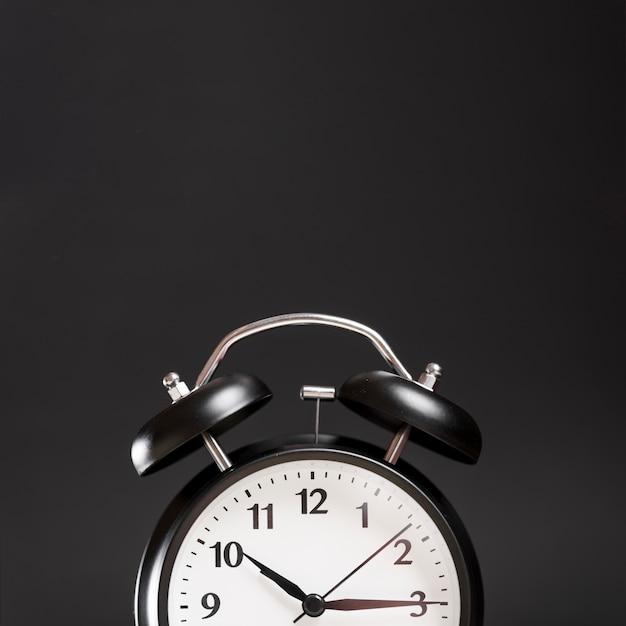 Primer plano de un reloj de alarma contra el fondo negro Foto gratis