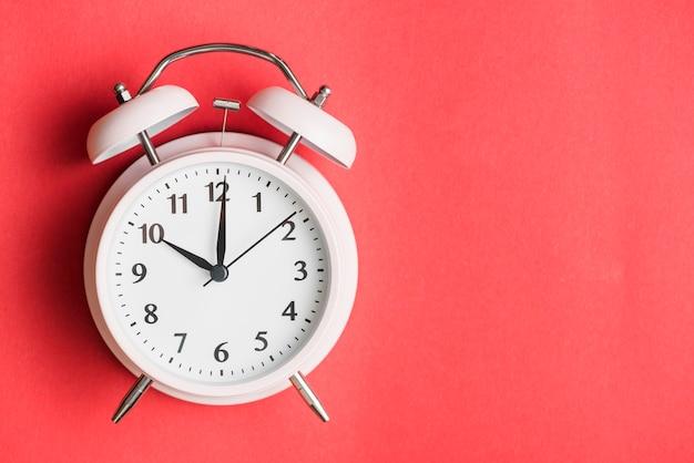 Primer plano de un reloj de alarma sobre fondo rojo Foto Premium