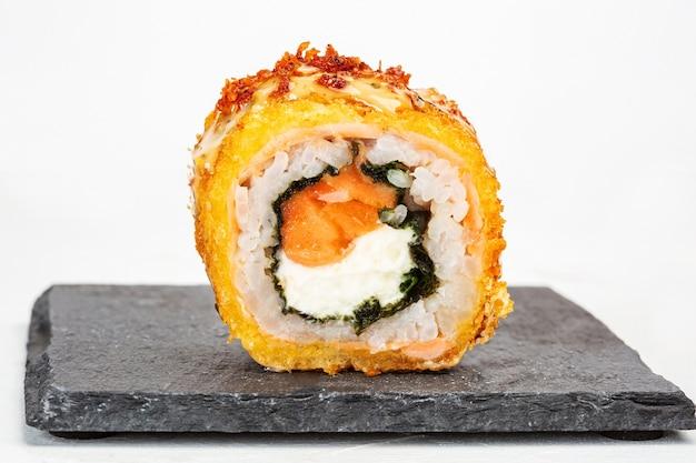 Primer plano de un rollo de sushi sobre una placa de piedra negra Foto gratis