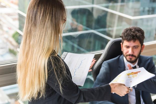 Primer plano de la secretaria de sexo femenino que da el mapa al encargado de sexo masculino en el lugar de trabajo Foto gratis