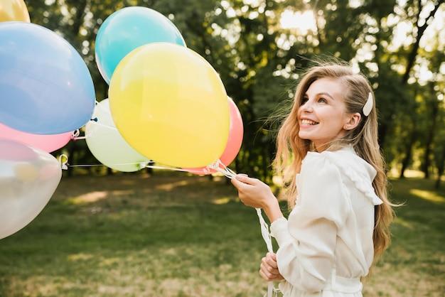 Primer plano sonriente cumpleañera con globos Foto gratis