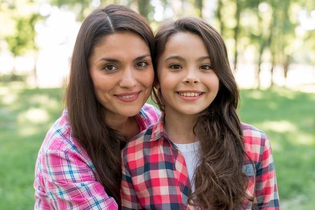 Primer plano de sonriente madre e hija de pie juntos en el parque Foto gratis