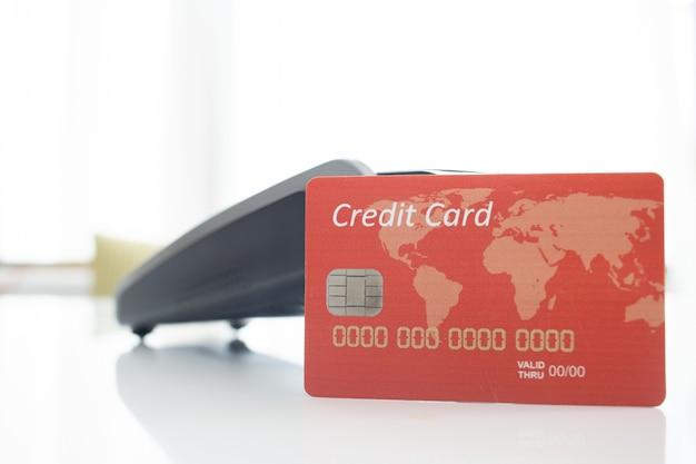 Primer plano de una tarjeta de crédito roja con un terminal de pago y un fondo blanco borroso Foto gratis
