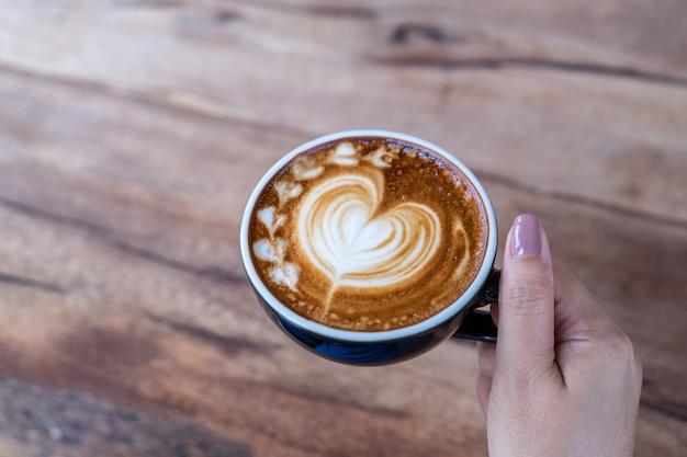 Primer plano de una taza de arte latte de café en mano de mujer en cafetería cafetería Foto gratis