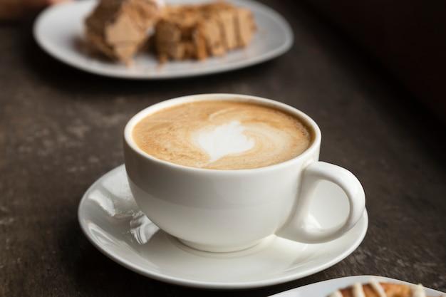 Primer plano de una taza de café y dulces Foto gratis