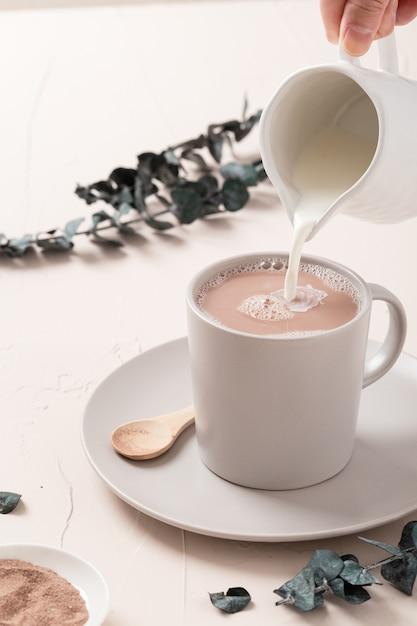Primer plano de una taza de café con leche y algunas decoraciones sobre una mesa blanca Foto gratis