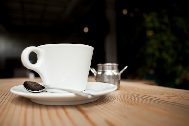 Primer plano de la taza de café en la mesa en la cafetería Foto gratis