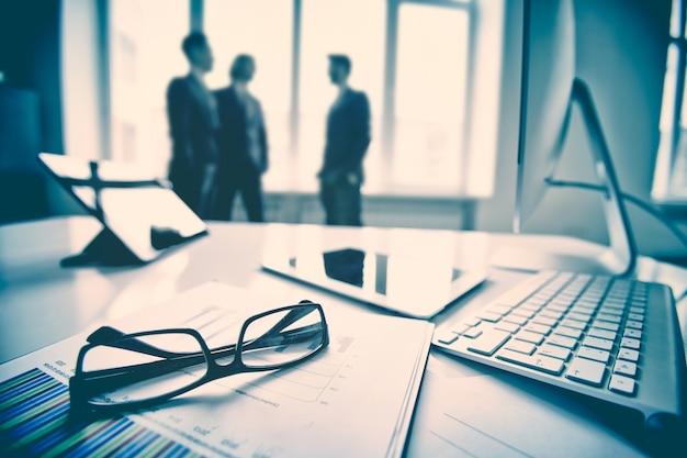 Primer plano de teclado y gafas con ejecutivos de fondo Foto gratis