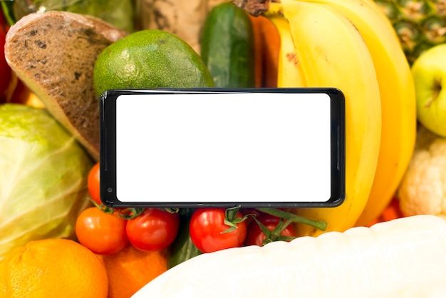 Primer plano de teléfono inteligente en frutas y verduras Foto gratis