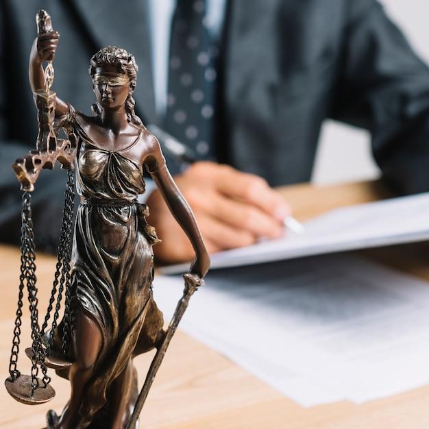 Primer plano, de, themis, o, dama, justicia, tenencia, escala, delante de, abogado, trabajando, en, escritorio Foto gratis