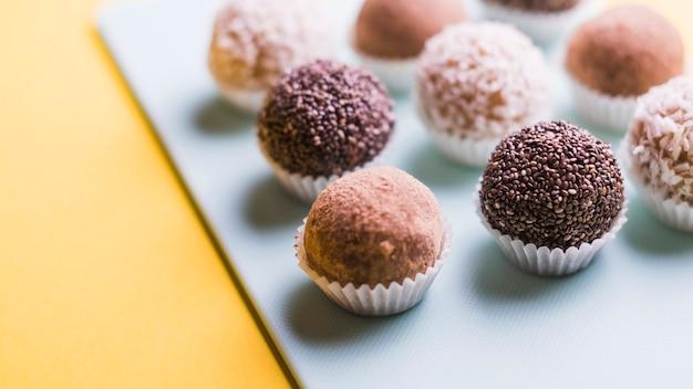 Primer plano de trufas de chocolate en bandeja blanca sobre fondo amarillo Foto gratis