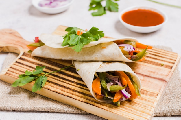 Primer plano de vegetales orgánicos envueltos en pita con salsa Foto gratis