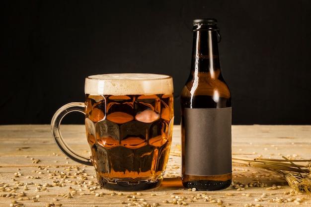 Primer plano de vidrio alcohólico y botella con espigas de trigo en superficie de madera Foto gratis