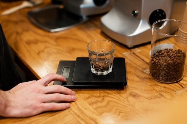 Primer plano de vidrio con granos de café en escala Foto gratis